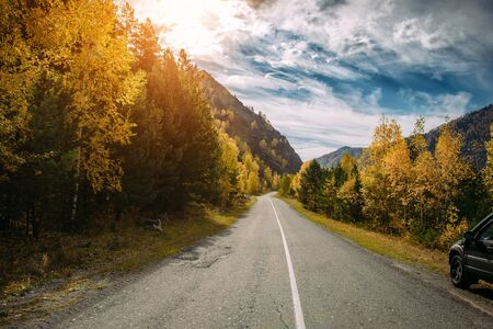 Photo pour Asphalt mountain road among the yellow autumn birches and high rocks in bright rays of setting sun. Concept of active and automobile tourism. - image libre de droit
