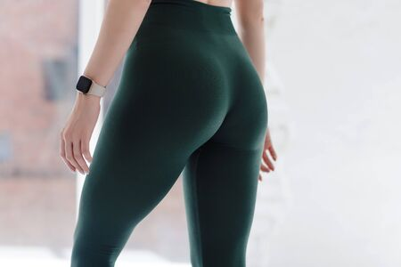 Photo pour Girl with beautiful sporty bump, hips. Close up. Green leggings. Health concept, workout, lifestyle, weight control, diet. Copy space. Body part. Front view. - image libre de droit