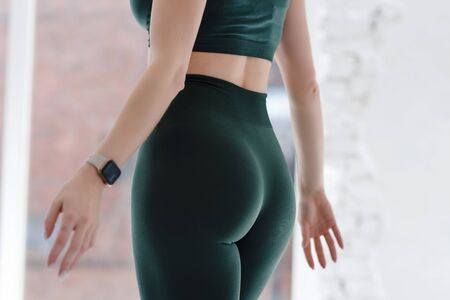 Photo for Girl with beautiful sporty bump, hips. Close up. Green leggings. Health concept, workout, lifestyle, weight control, diet. Copy space. Body part. Front view. - Royalty Free Image