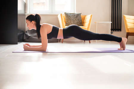 Foto für Beautiful strong woman in sport clothes standing in plank position on yoga mat. Active brunette doing abs exercises while staying at home. - Lizenzfreies Bild