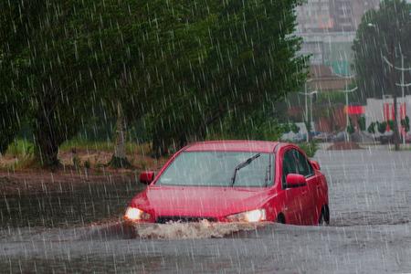 Foto de car rides in heavy rain on a flooded road. - Imagen libre de derechos