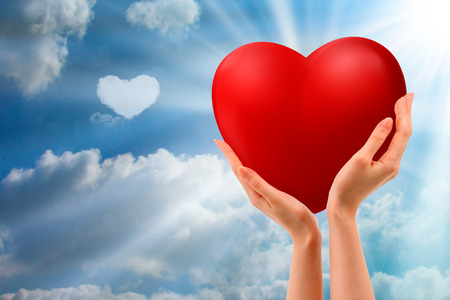 Photo pour hand holding up red heart against a blue sky with clouds - image libre de droit