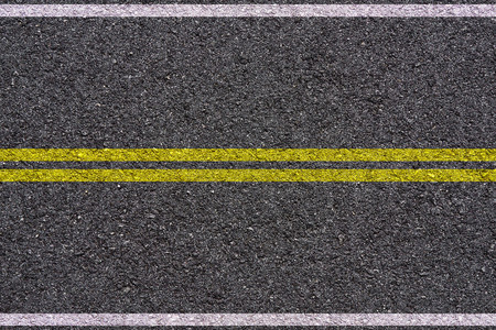 Yellow and white double lines on asphalt background