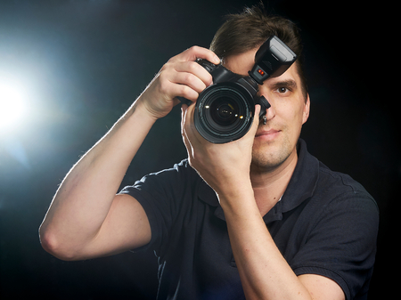 Male photographer taking a picture with a lightning in the background
