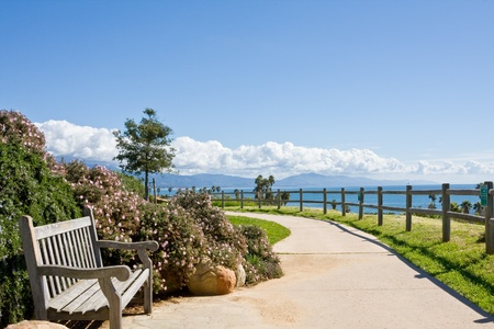 A bench and sidewalk in a public park along the coast in Santa Barbara, California.