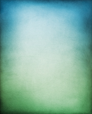 Photo pour A textured paper backgrouund with a green to blue gradation. - image libre de droit
