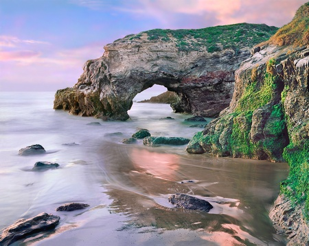 A natural arch along the Pacific coastline near Santa Barbara, California.  Image made during an extreme low tide at sunset.