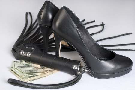 Strict Black Leather Flogging Whip, high heels shoes and money on white background. Not isolated.
