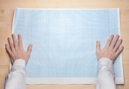 Foto de two man hands holding empty blueprint canvas - Imagen libre de derechos