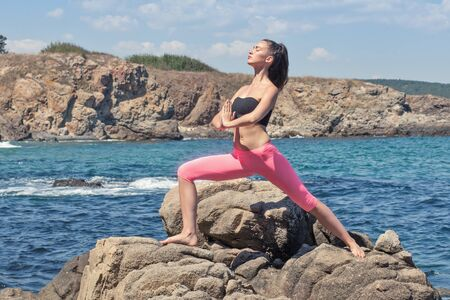 young beautiful fit brunette doing yoga on sea rocky coastline
