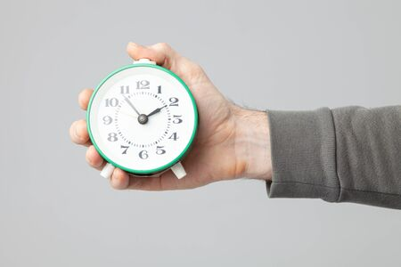 Photo pour male hand holding vintage alarm clock isolated on gray background - image libre de droit