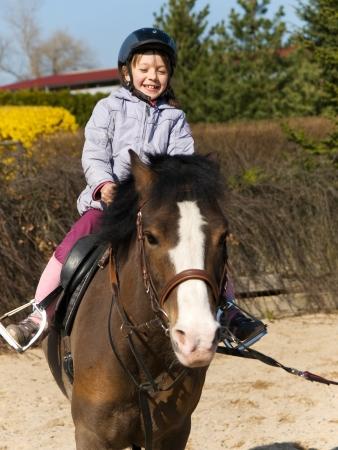Happy little girl riding on ponny horse