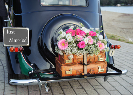 Photo pour Wedding bouquet on vintage wedding car - image libre de droit