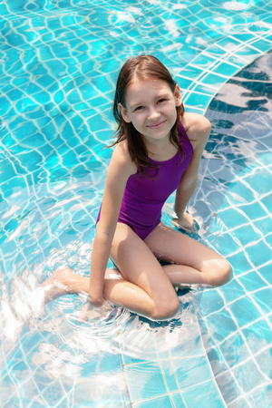 Foto de Cute smiling preteen girl sitting at swimming pool edge. Travel, vacation, childhood concept - Imagen libre de derechos