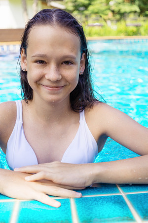 Photo pour Cute smiling preteen girl at swimming pool edge. Travel, vacation, childhood concept - image libre de droit