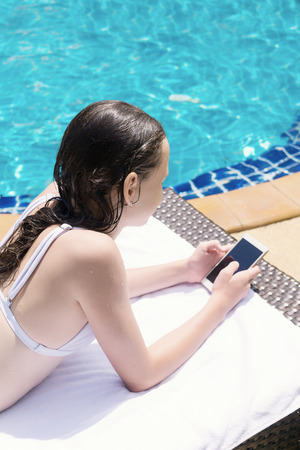 Foto de preteen girl in bikini lying in lounge chair with cellphone by the pool. Vacation, travel, healthy lifestyle concept. Text space - Imagen libre de derechos