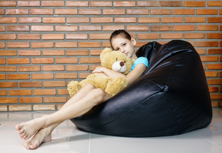 Photo pour beautiful caucasian teen girl sitting in black bean bag chair against brick wall. Casual outfit. Childhood concept - image libre de droit