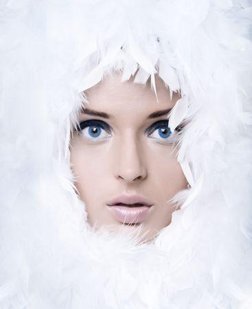 Closeup portrait of beautiful girl witk white feathers