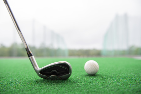 Foto de Golf club and ball on a synthetic grass mat at a practice range. - Imagen libre de derechos