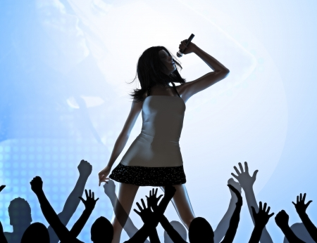 Female singer on stage performing infront of a crowd