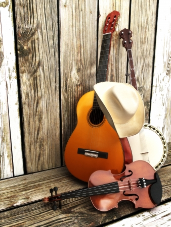 Country music background with stringed instruments  Guitar, banjo, violin and a cowboy hat leaning against a wood fence  Room for text or copy space