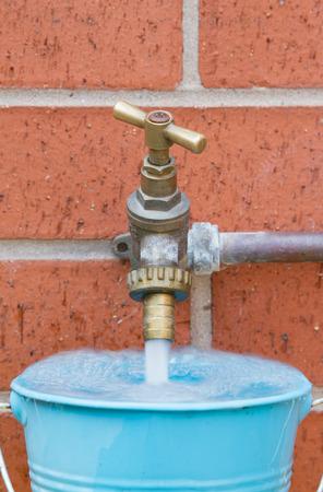 Outside tap on brick wall filling a blue bucket