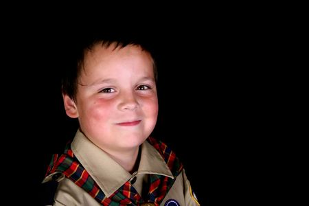 Young boy wearing a beige shirt and plaid scarf isolated on black background