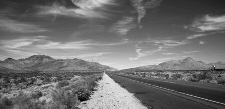 Black and white road with a semi truck heading to the horizon