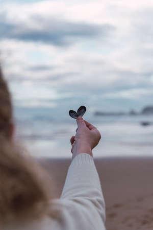 Foto de Woman holding a heart shaped shell in front of the sea - Imagen libre de derechos