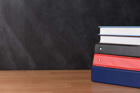 Photo pour A stack of three different binders on desk in front of black board with two books. - image libre de droit
