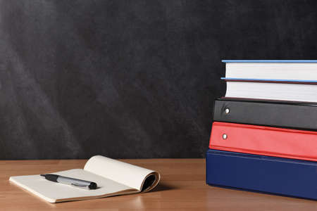 Photo for A stack of three different binders on desk in front of black board with two books and note pad and pen. - Royalty Free Image