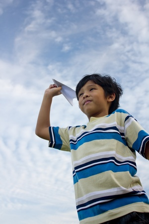 An asian boy playing paper aeroplane, a concept of dream & ambition