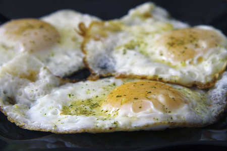 Morning roasted whole eggs on the black plate and dill over