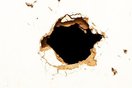Hole in the fibreboard on black background.