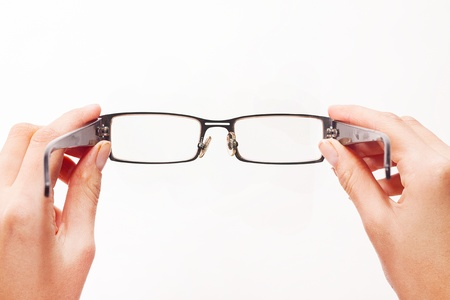 Hands holding eyeglasses on white background