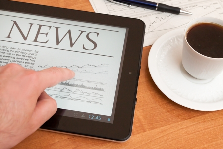 Tablet PC shows latest news on screen, which lying on work place