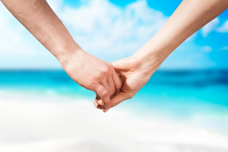 Holding hands couple on beach  Romantic love and happiness