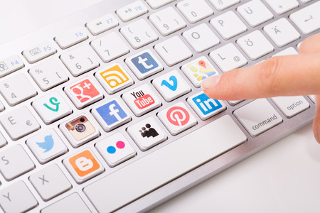 Photo for BELCHATOW, POLAND - AUGUST 31, 2014: Male hand pointing on key with a social media logotype collection printed and placed on modern computer keyboard. - Royalty Free Image