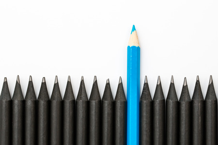 Blue pencil standing out from the row of black pencils.