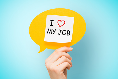 Foto de Adhesive note on yellow speech bubble with I love my job words on blue background. - Imagen libre de derechos