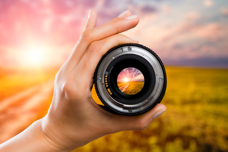 Photo for photography view camera photographer lens lense through field sunrise sunset sun sky cloud video photo digital glass hand blurred focus people concept - stock image - Royalty Free Image