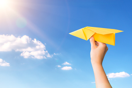 paper travel sky plane child flying yellow fun human leisure kid throw view throwing handmade freedom object up air airline joy concept - stock image