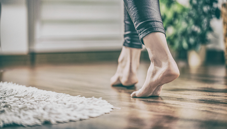 Foto de Floor heating. Young woman walking in the house on the warm floor. Gently walked the wooden panels. - Imagen libre de derechos