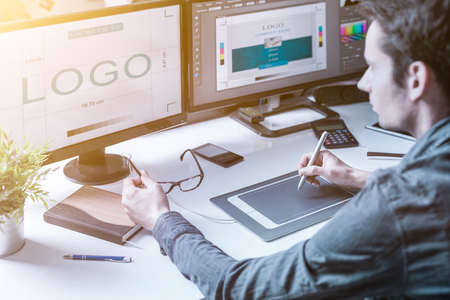 Photo for Computer graphic designer designs logos and advertising graphics. Draws a logo on the graphics tablet. - Royalty Free Image