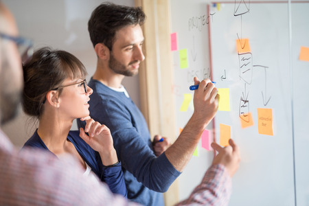 Foto de Business people meeting at office and use sticky notes to share idea. Brainstorming concept. Sticky note on glass wall. - Imagen libre de derechos