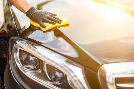 Foto de Car detailing - the man holds the microfiber in hand and polishes the car. Selective focus. - Imagen libre de derechos