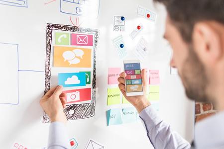 Foto de Designer man drawing website ux app development and holding smart phone on hand. User experience concept. - Imagen libre de derechos