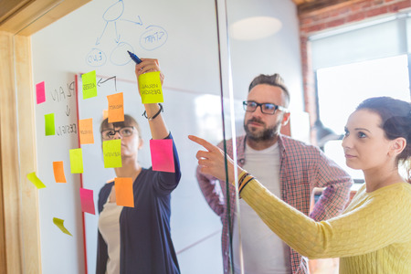 Foto de Business people meeting at office and use post it notes to share idea. Brainstorming concept. Sticky note on glass wall. - Imagen libre de derechos