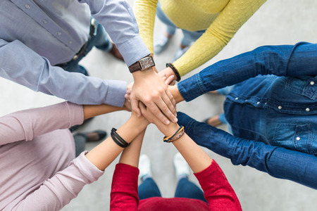 Foto de Close up top view of young business people putting their hands together. Stack of hands. Unity and teamwork concept. - Imagen libre de derechos