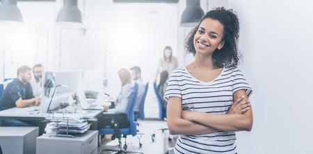Foto de Portrait of young confident woman leader standing in office. New start up business concept. - Imagen libre de derechos